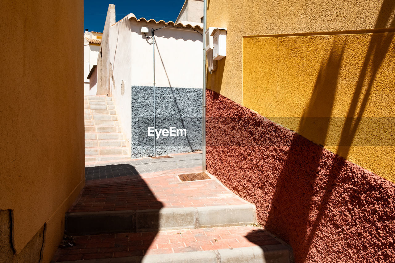 sunlight, architecture, shadow, drying, nature, no people, hanging, built structure, day, building exterior, textile, wall - building feature, wall, clothesline, building, laundry, window, outdoors, clothing, house