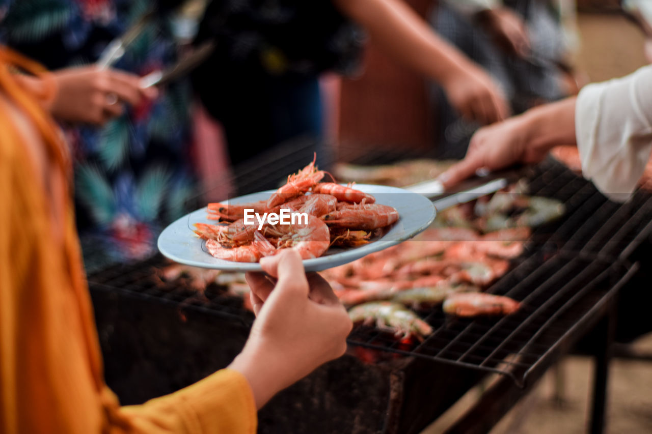 People standing by barbecue grill