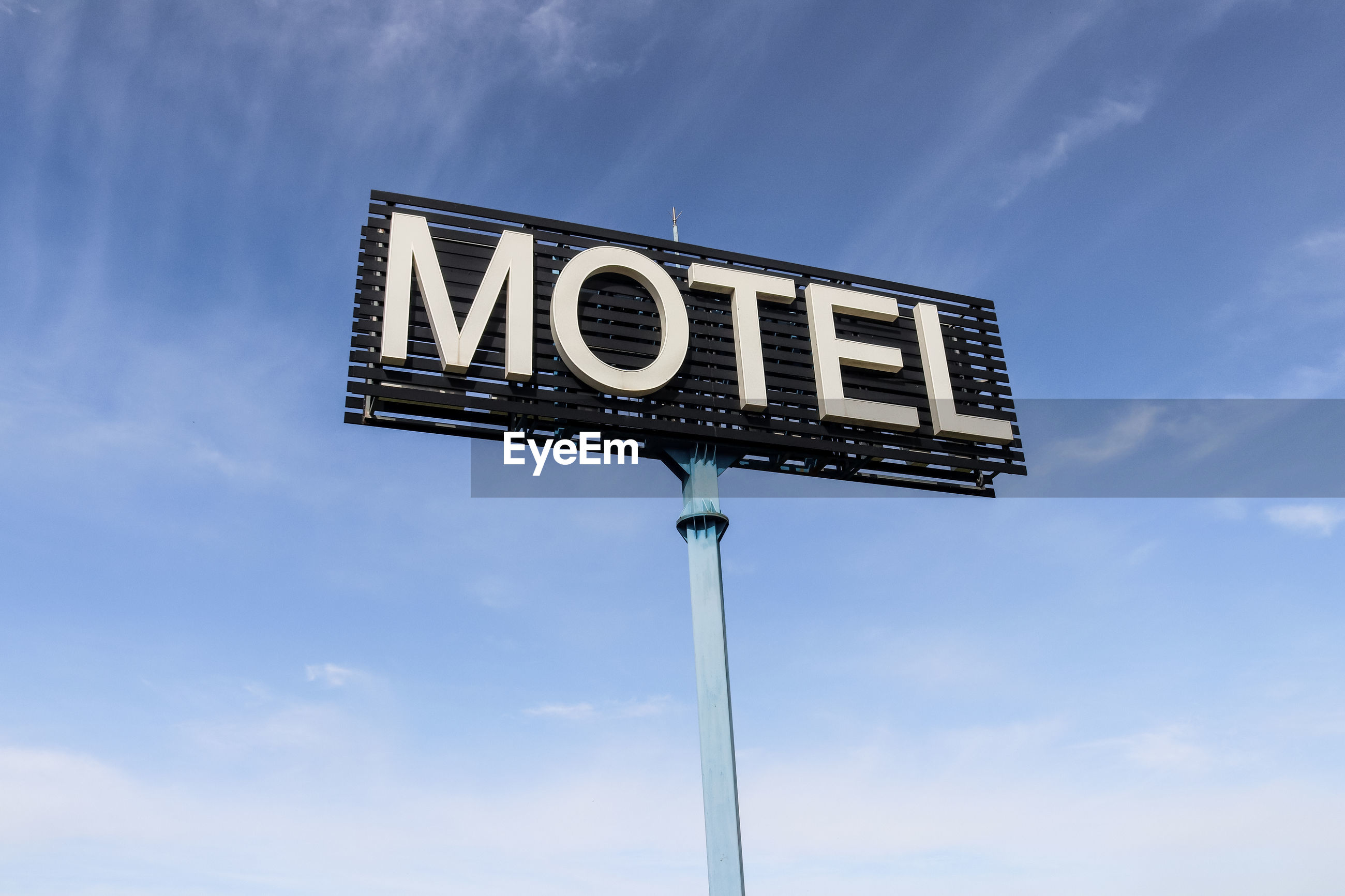 Low angle view of motel sign against blue sky
