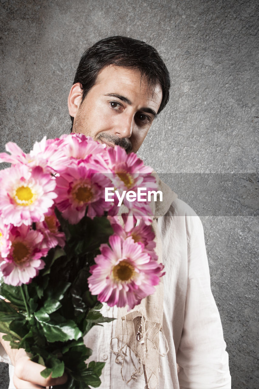 Portrait of man holding pink flowers bouquet while standing against wall