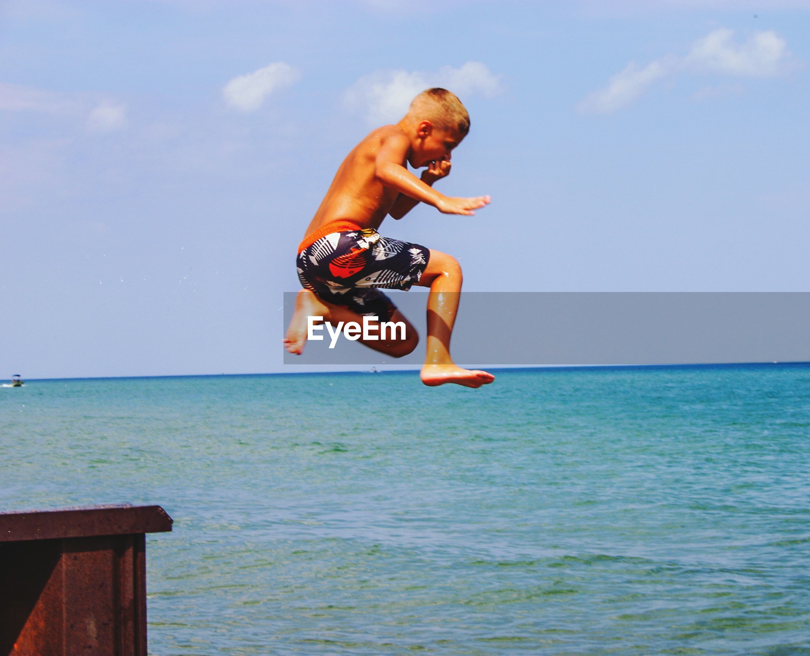 Shirtless boy jumping in sea against sky
