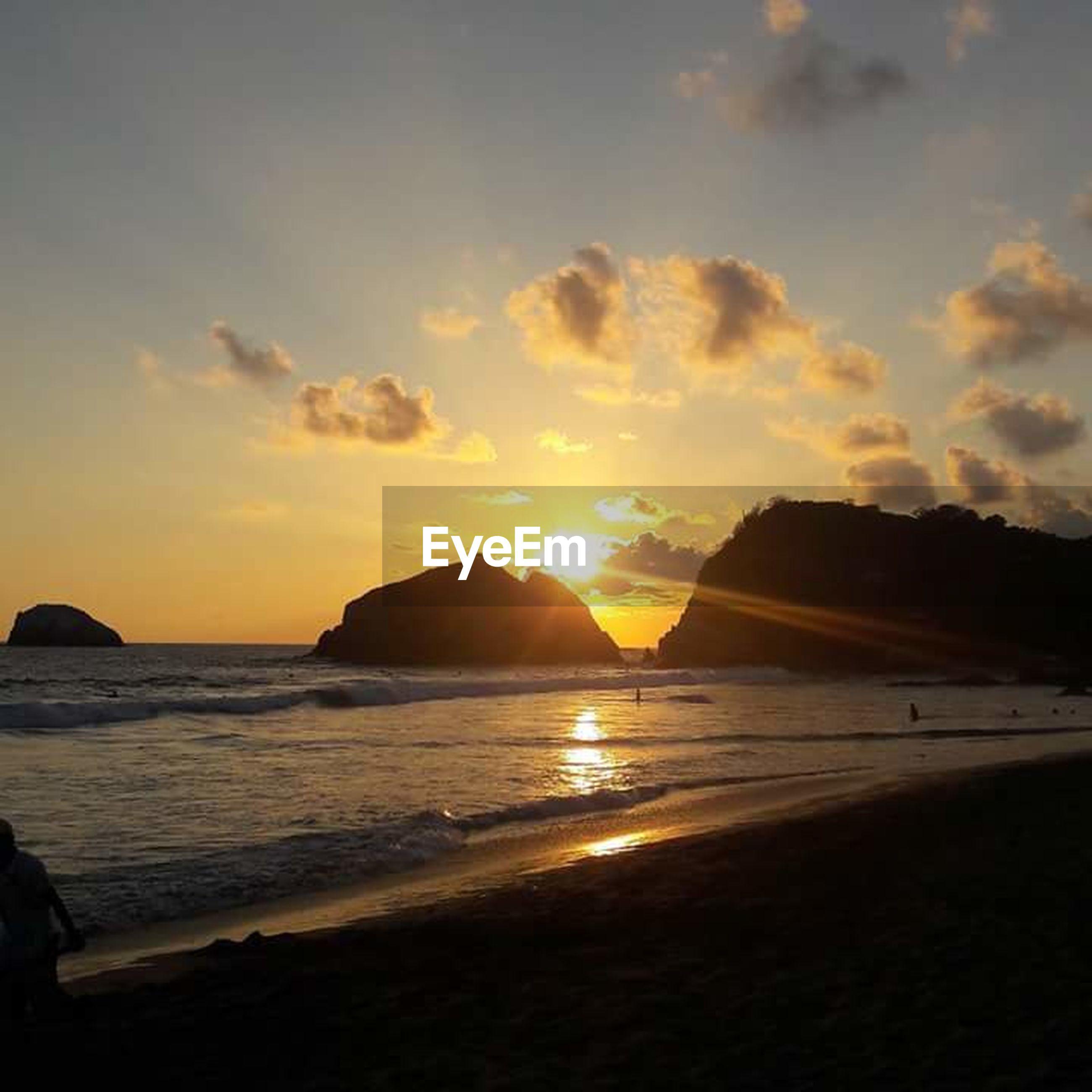 sunset, sea, beach, water, scenics, sun, tranquil scene, beauty in nature, shore, tranquility, sky, silhouette, horizon over water, idyllic, nature, mountain, orange color, sunlight, sand, coastline