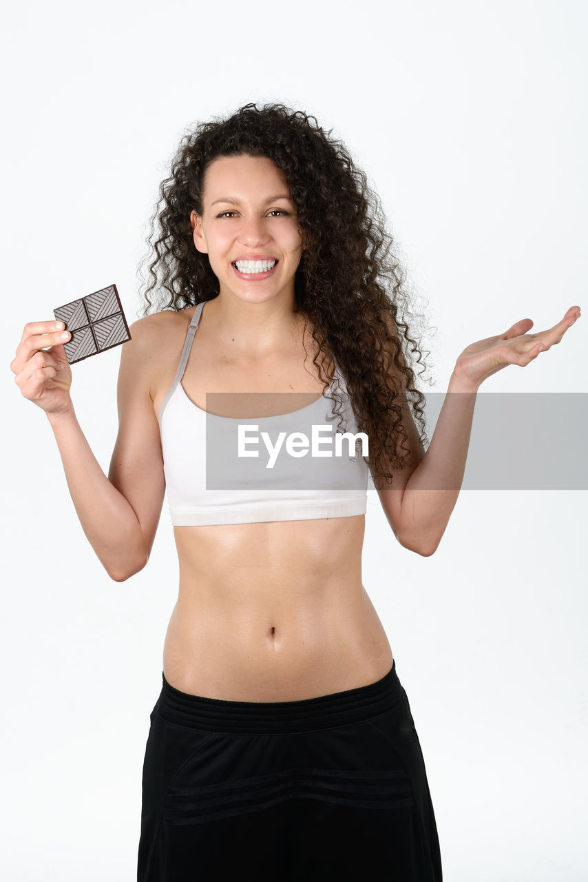 Portrait Of Smiling Woman Holding Chocolates Against White Background