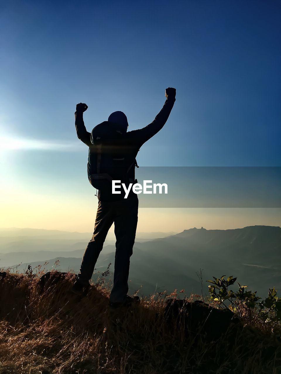 Full Length Of Man Standing On Mountain Against Sky