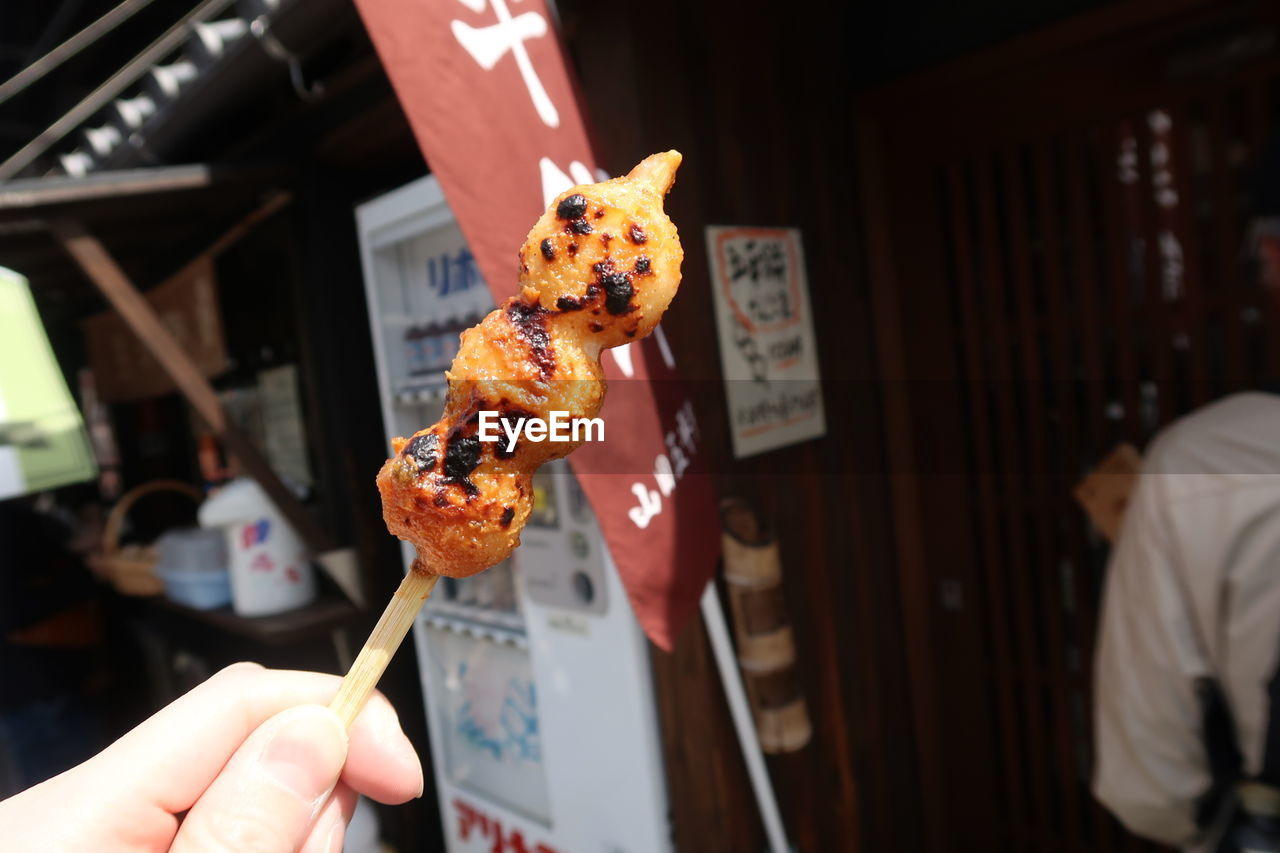 food and drink, food, holding, focus on foreground, indoors, freshness, human hand, lifestyles, real people, meat, skewer, unhealthy eating, one person, close-up, indulgence, human body part, incidental people, men, hand, japanese food, finger