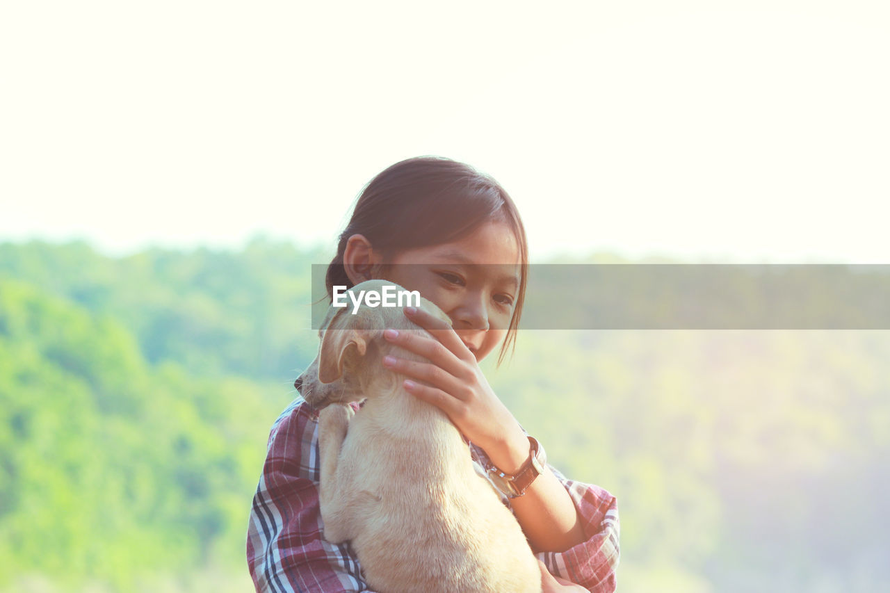 Girl playing with puppy against clear sky
