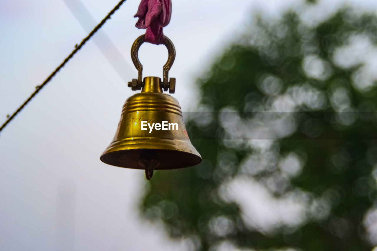 focus on foreground, bell, metal, hanging, gold colored, no people, low angle view, outdoors, day, close-up, belief, lighting equipment, nature, decoration, religion, sky, spirituality, tree, branch, shape, electric lamp