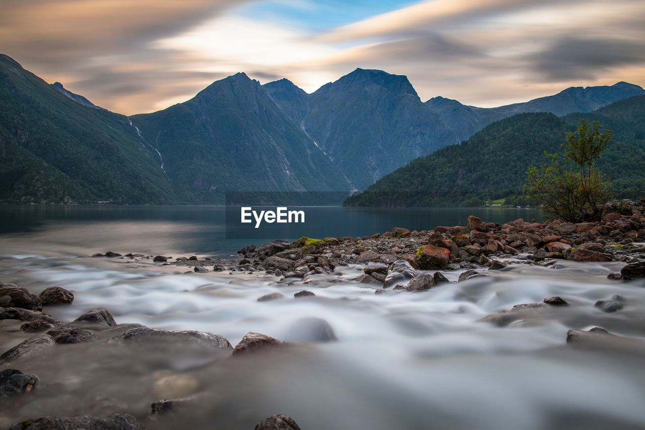 River flowing over rocks against mountain