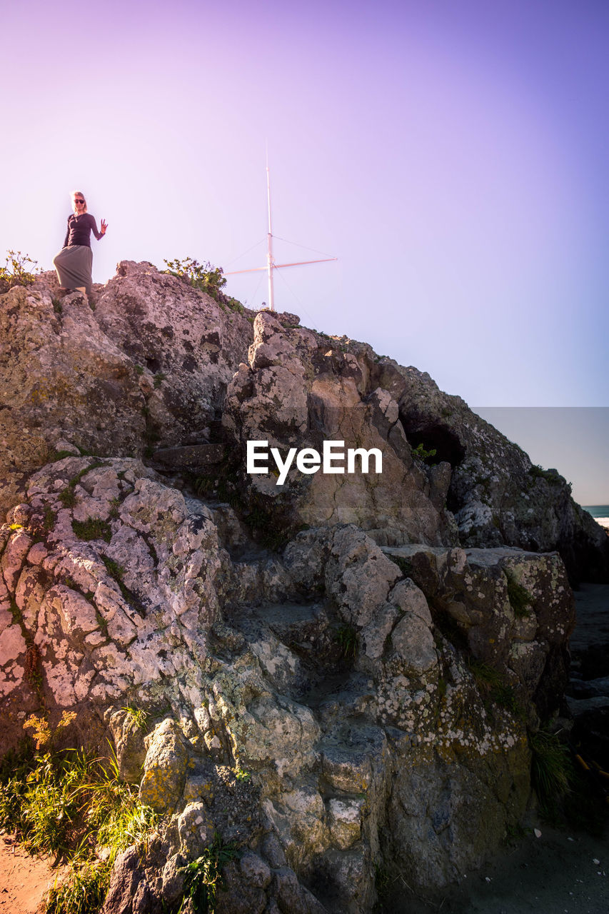 rock - object, rock formation, wind power, wind turbine, beauty in nature, mountain, sky, clear sky, alternative energy, nature, real people, outdoors, low angle view, fuel and power generation, scenics, men, one person, cliff, built structure, day, architecture, technology, building exterior, windmill, full length, people