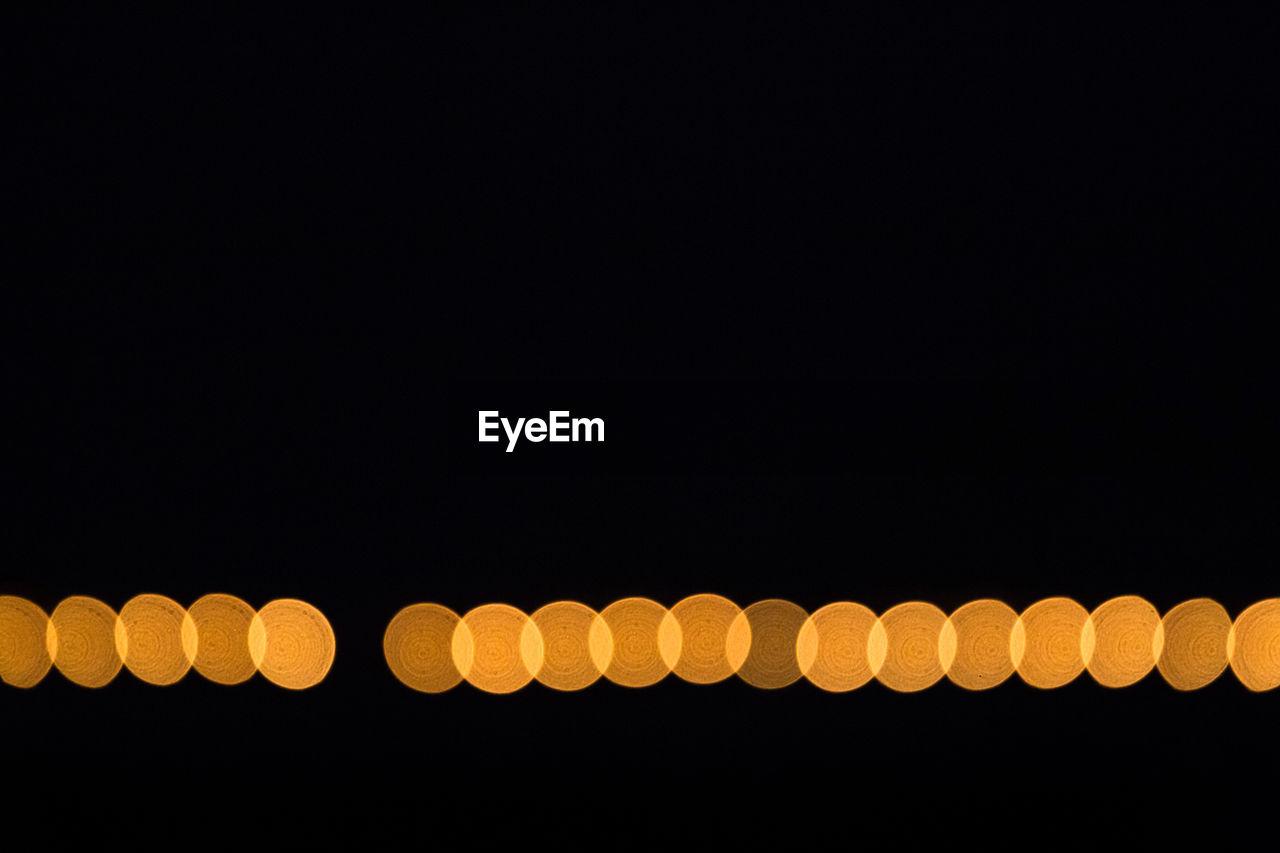 Defocused Image Of Orange Lights Against Clear Sky At Night