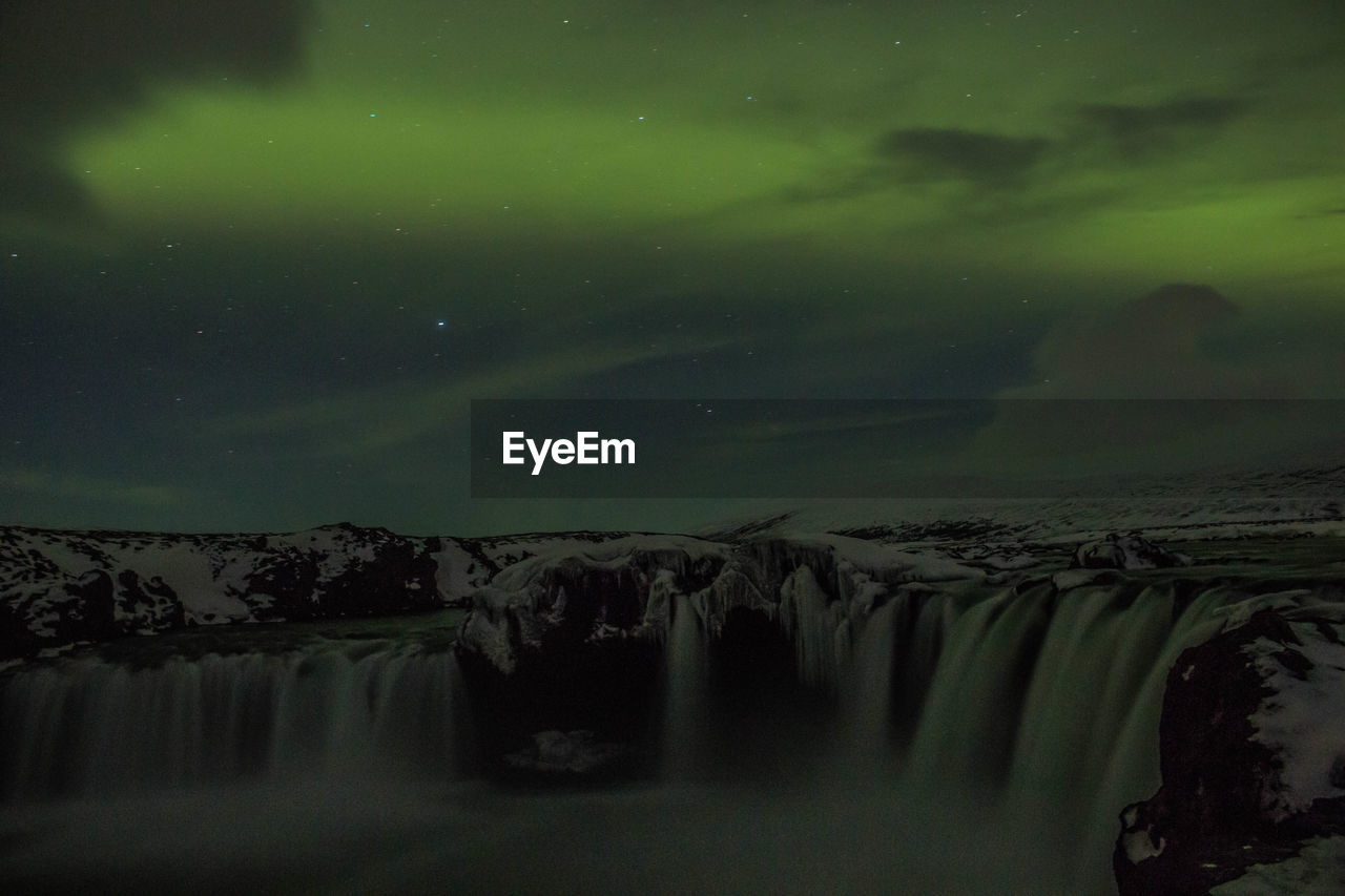 IDYLLIC SHOT OF WATERFALL AGAINST SKY AT NIGHT