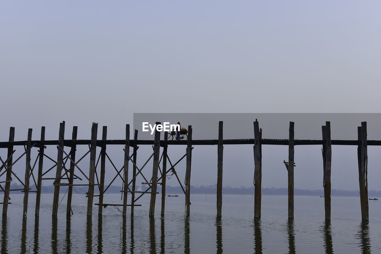 copy space, outdoors, nature, railing, sky, water, clear sky, sea, day, men, real people, scenics, full length, togetherness, wooden post, perching, beauty in nature, horizon over water, mammal, bird, people