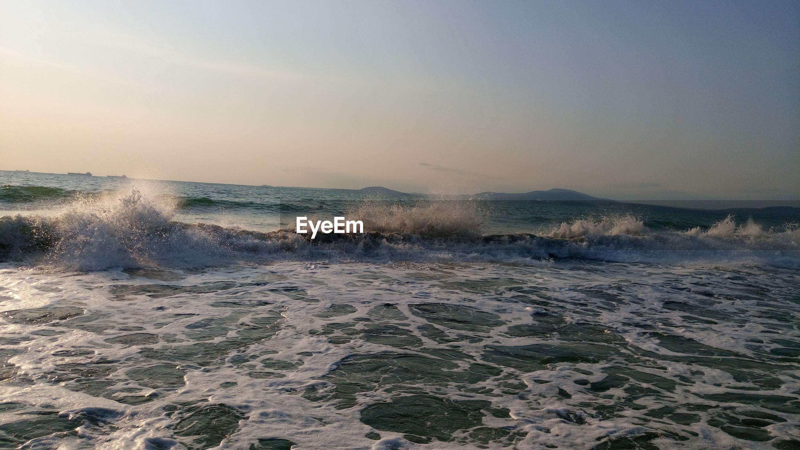 Waves splashing in sea against sky during sunset