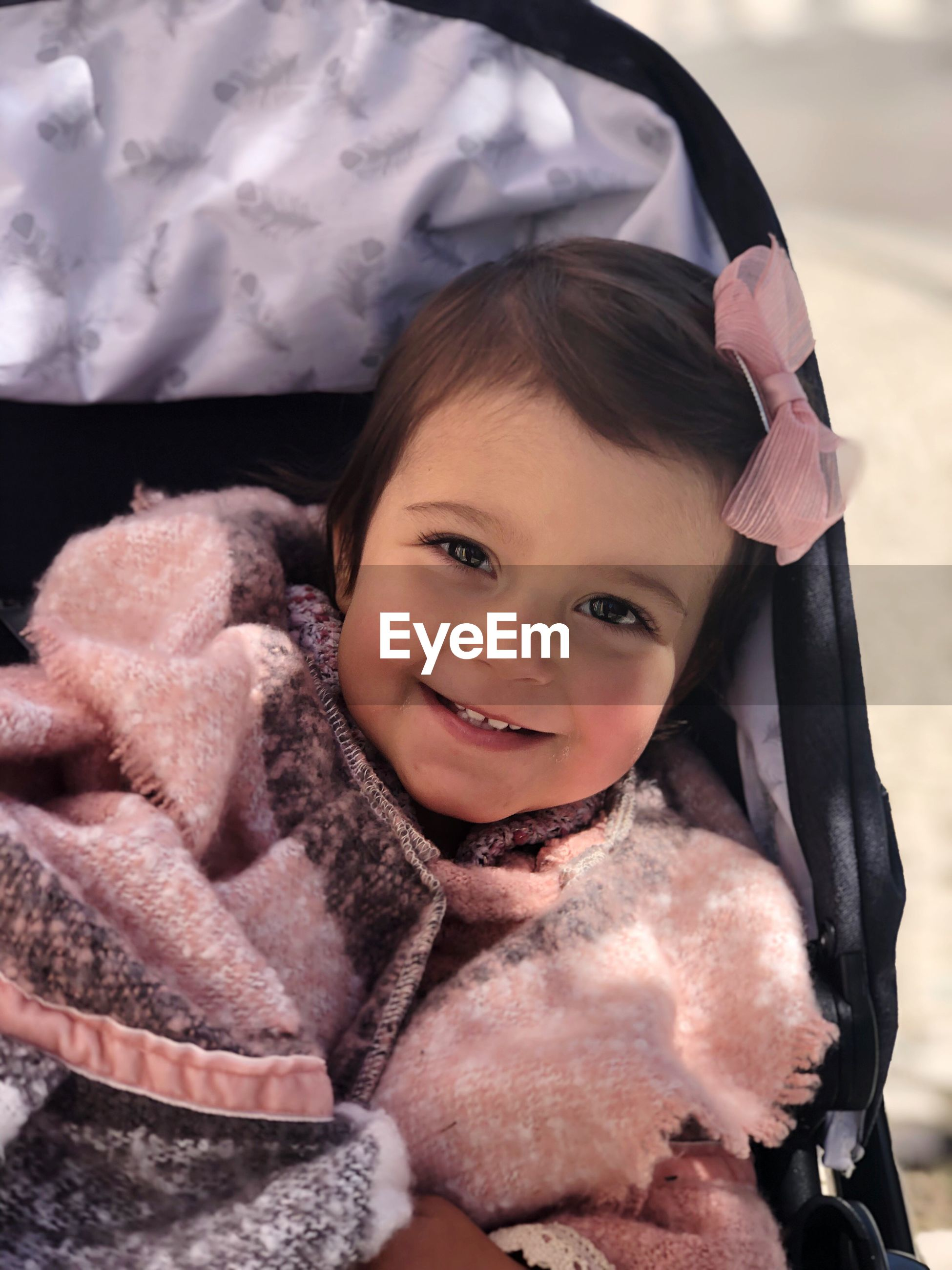 Portrait of cute baby girl smiling while sitting in baby stroller