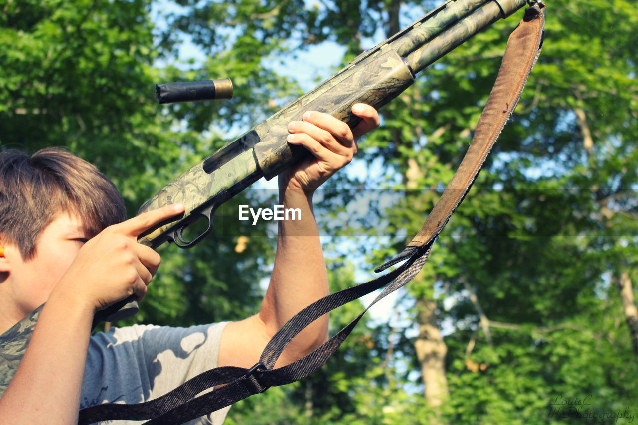 Teenage Boy Rifle Shooting Against Trees At Forest