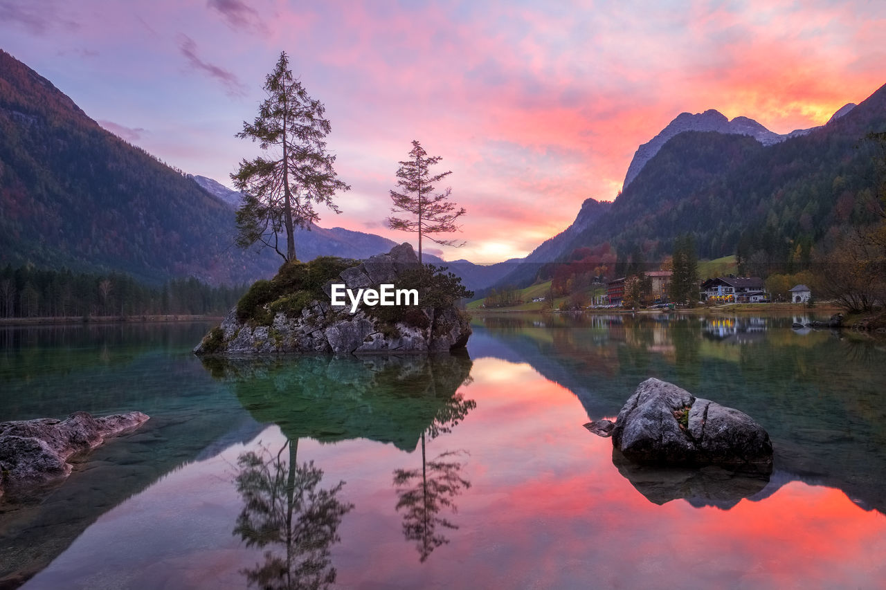 reflection, mountain, tranquil scene, sky, water, beauty in nature, scenics, rock - object, sunset, tranquility, nature, lake, mountain range, outdoors, cloud - sky, no people, tree, built structure, architecture, day
