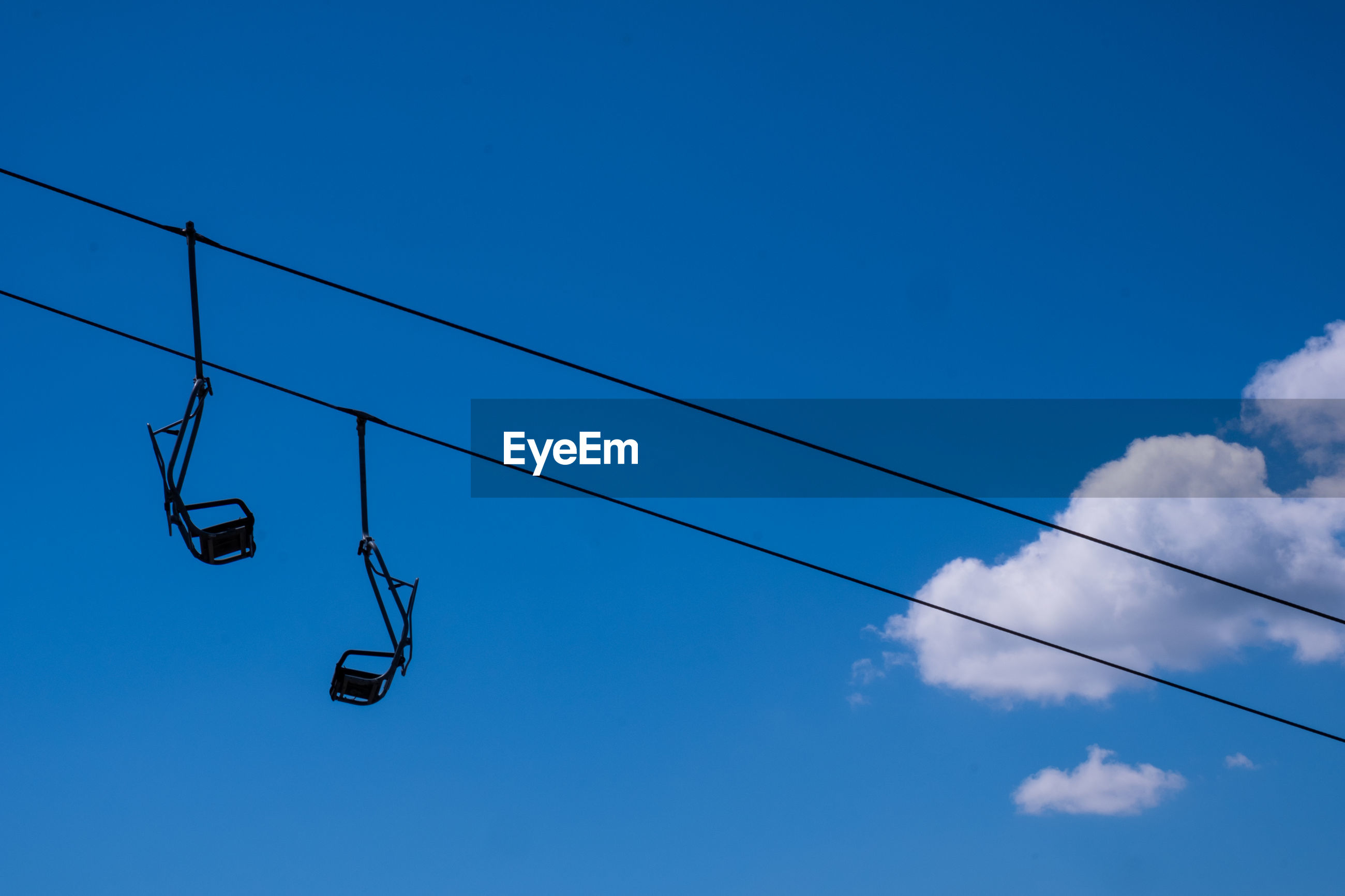 Low angle view of ski lifts against blue sky