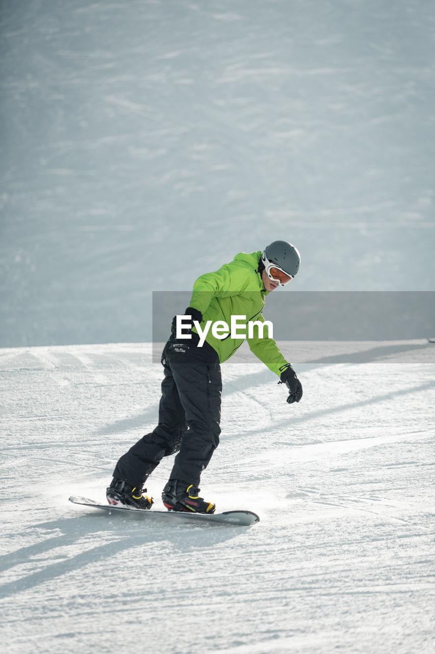Full length of man snowboarding on snow