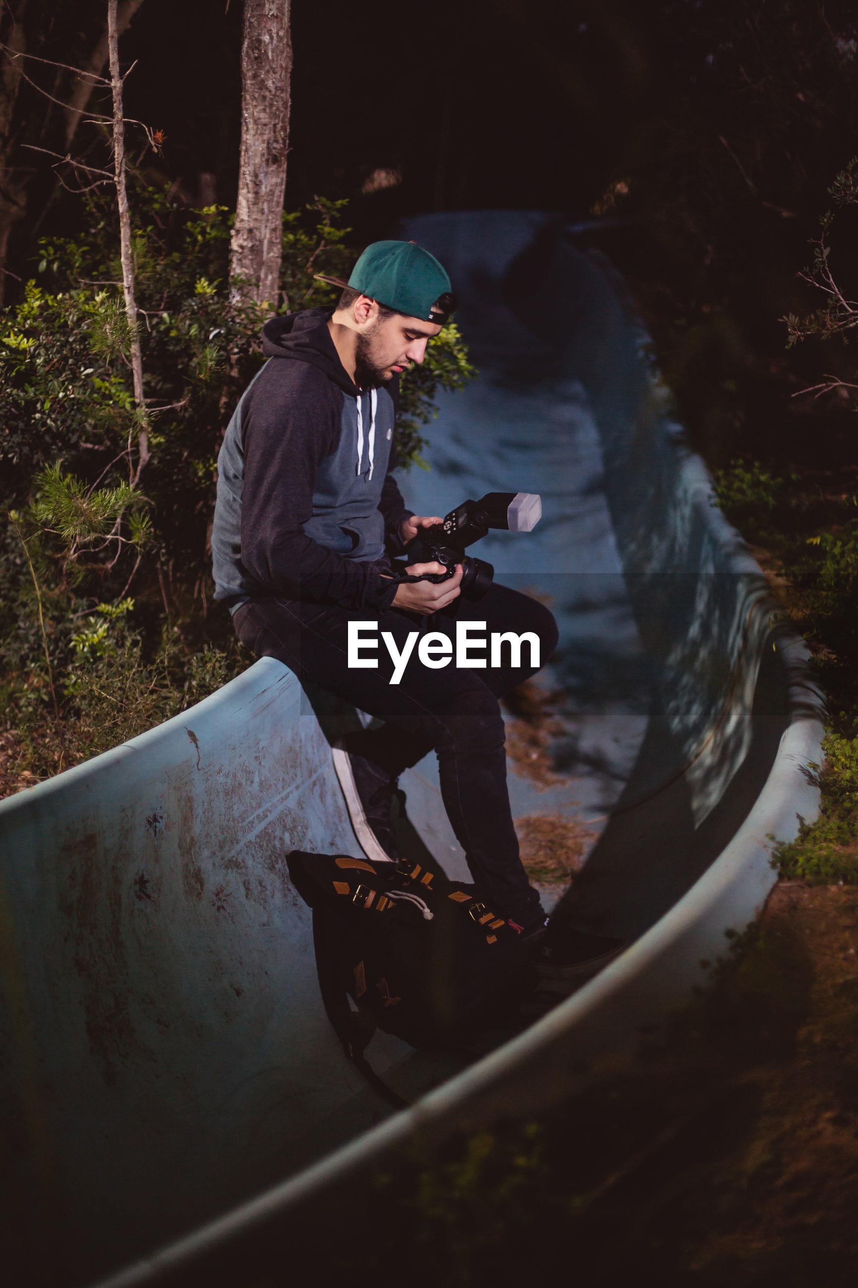 Photographer holding camera while sitting on slide at night