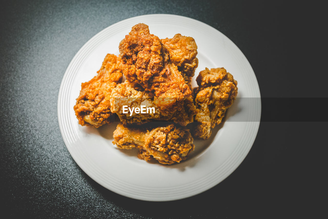High angle view of chicken wings in plate over black background