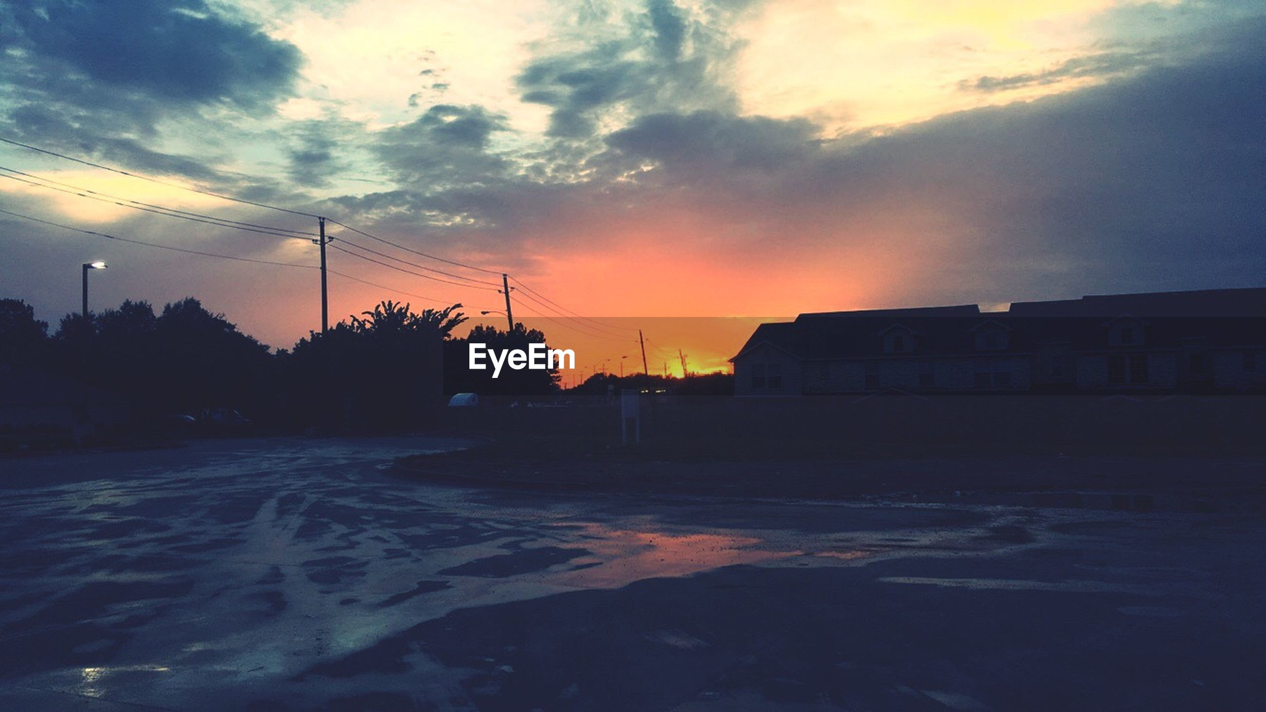 sunset, street, road, empty, transportation, cloud, silhouette, sky, long, tranquil scene, building exterior, orange color, outdoors, dark, nature, scenics, tranquility, the way forward, outline, cloud - sky, solitude, cloudy, beauty in nature, surface level, remote