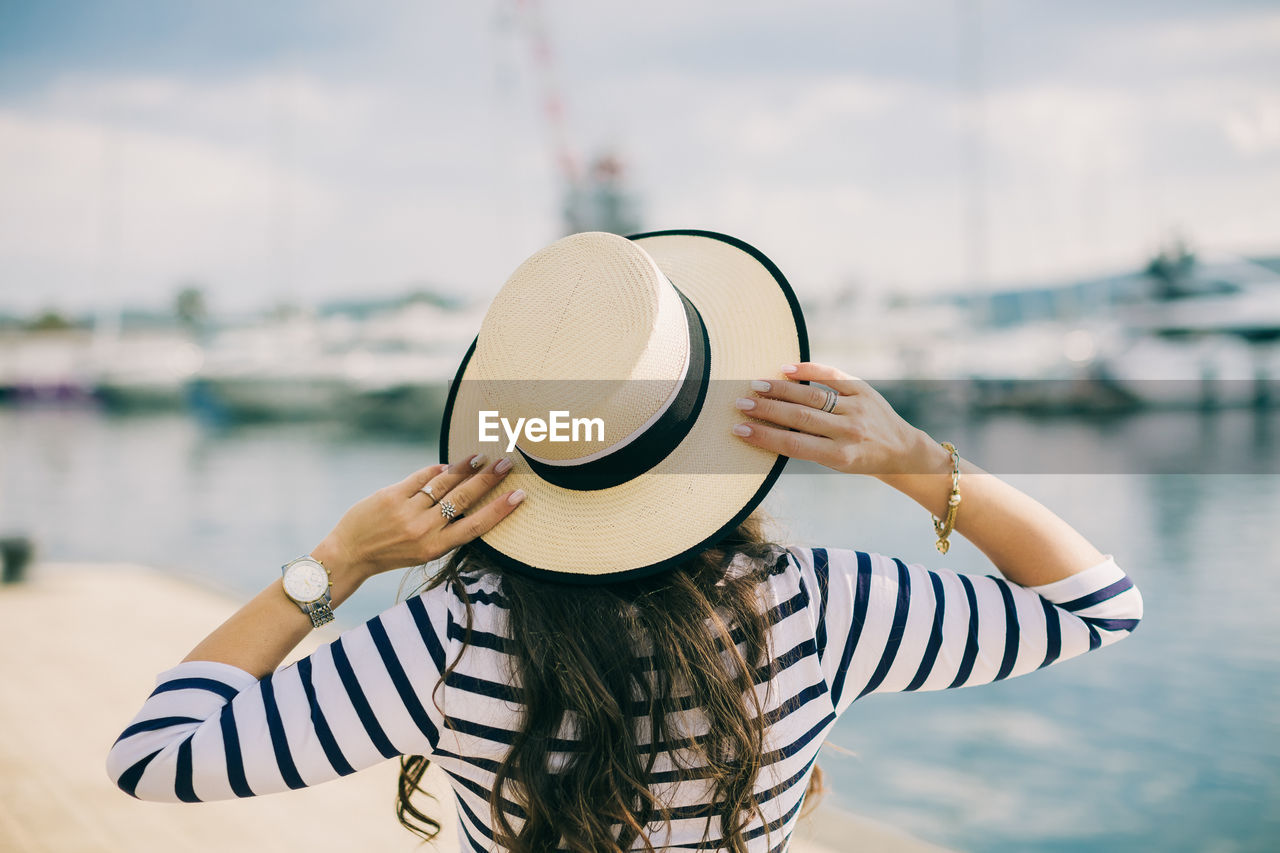 hat, straw hat, rear view, sun hat, focus on foreground, water, real people, one person, standing, outdoors, day, lifestyles, leisure activity, sea, women, nature, beauty in nature, sky, close-up