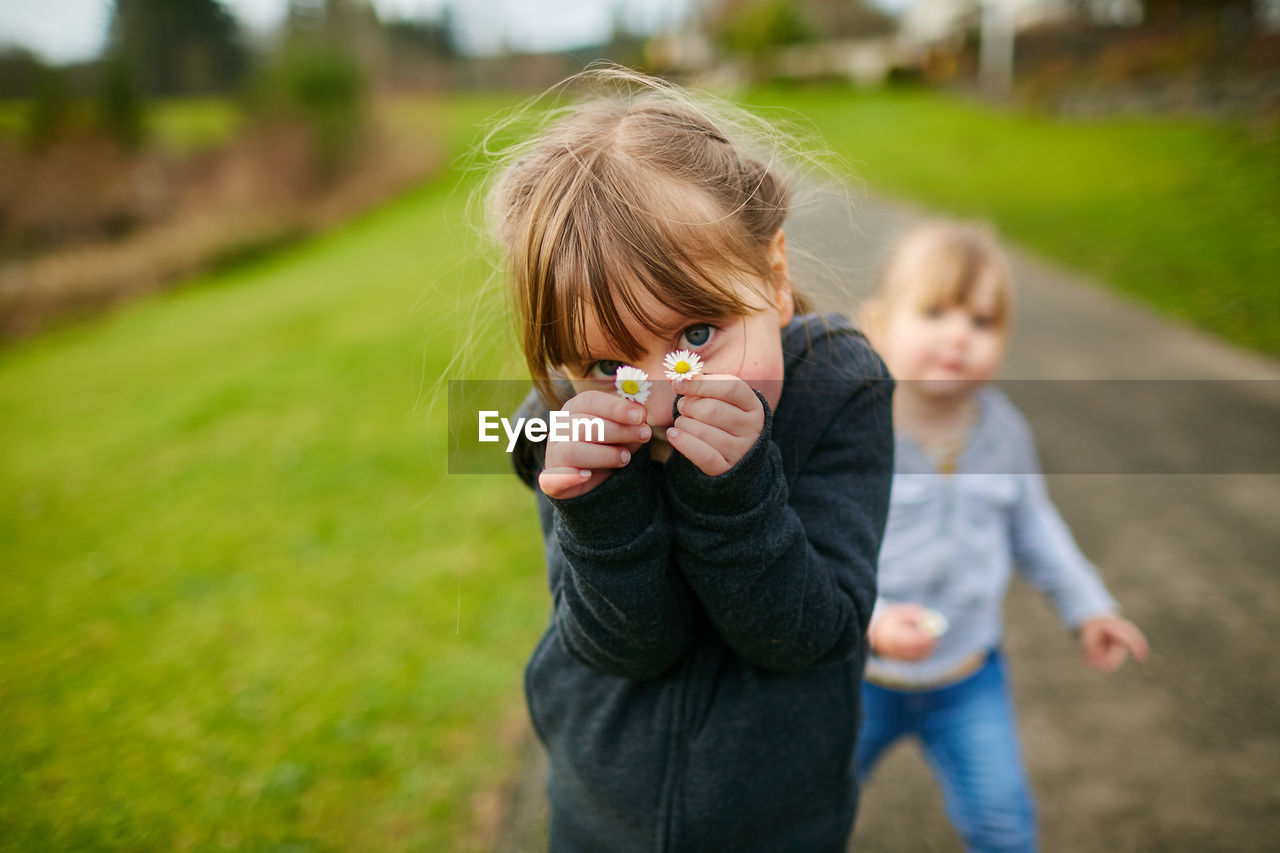 real people, childhood, child, two people, casual clothing, lifestyles, women, females, leisure activity, plant, focus on foreground, men, girls, day, blond hair, togetherness, boys, males, hair, innocence, outdoors, positive emotion
