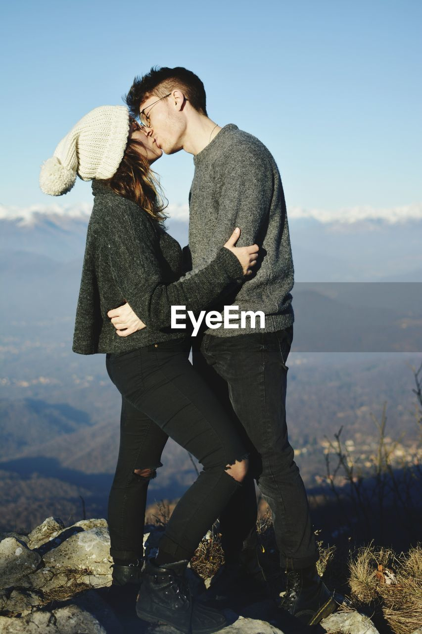 Side View Of Young Couple Kissing While Standing On Mountain Against Sky