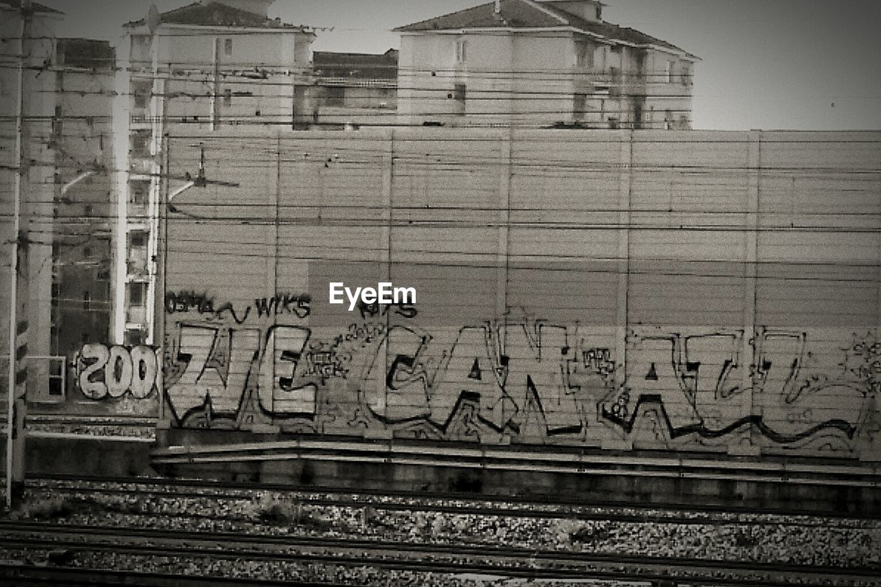 graffiti, text, architecture, day, outdoors, communication, rail transportation, built structure, no people, railroad track, building exterior, close-up