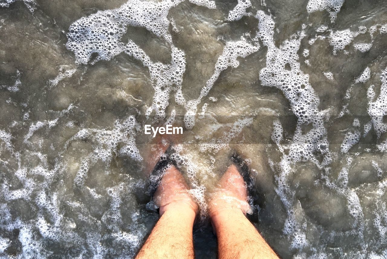 high angle view, real people, water, one person, day, outdoors, low section, sea, beach, directly above, wave, motion, lifestyles, nature, sand, men, close-up