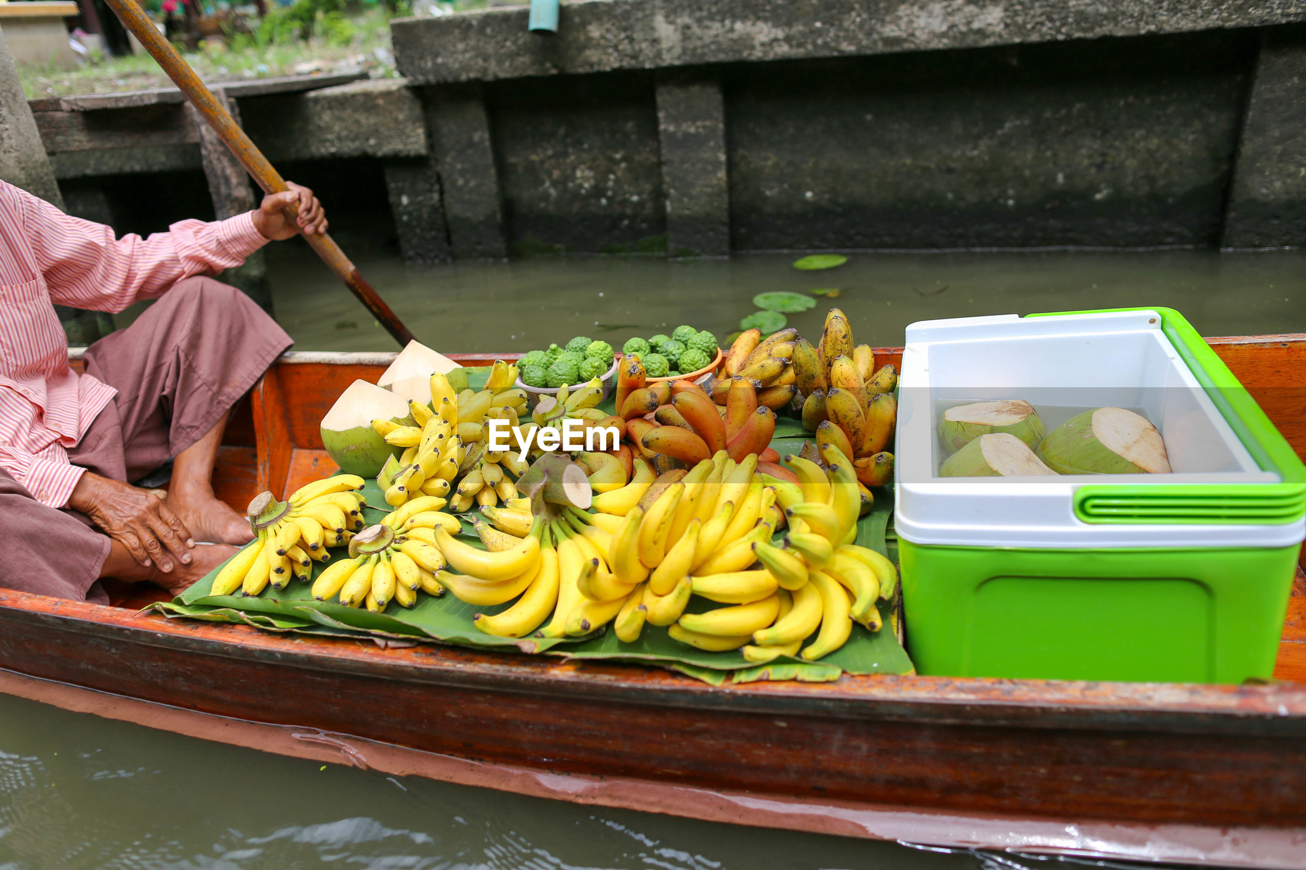 Low section of man with fruits sitting no boat in lake