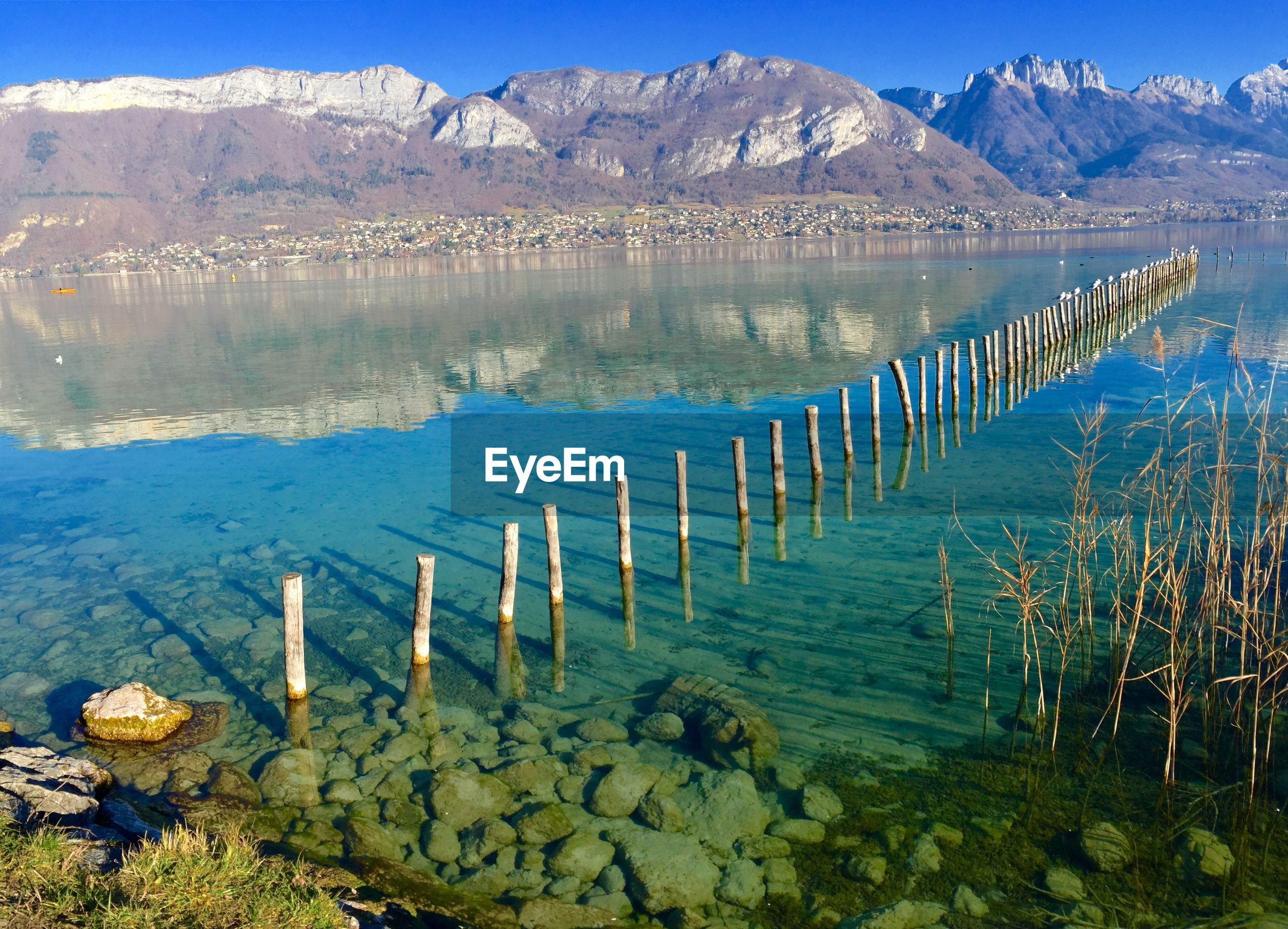 Wooden posts in lake against mountains