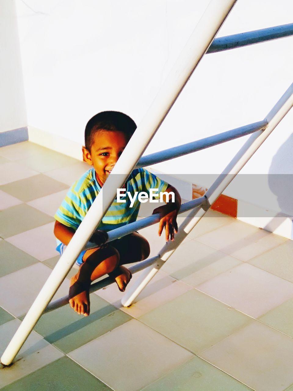 Boy Crouching On Ladder