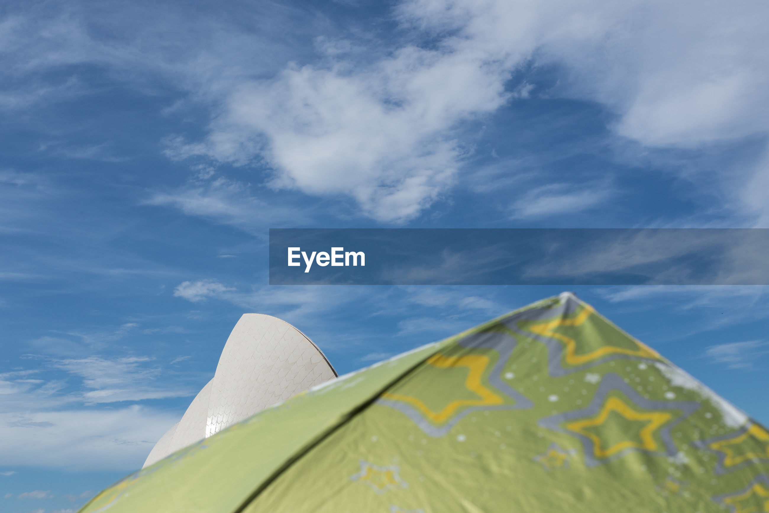 Low angle view of green umbrella against blue sky