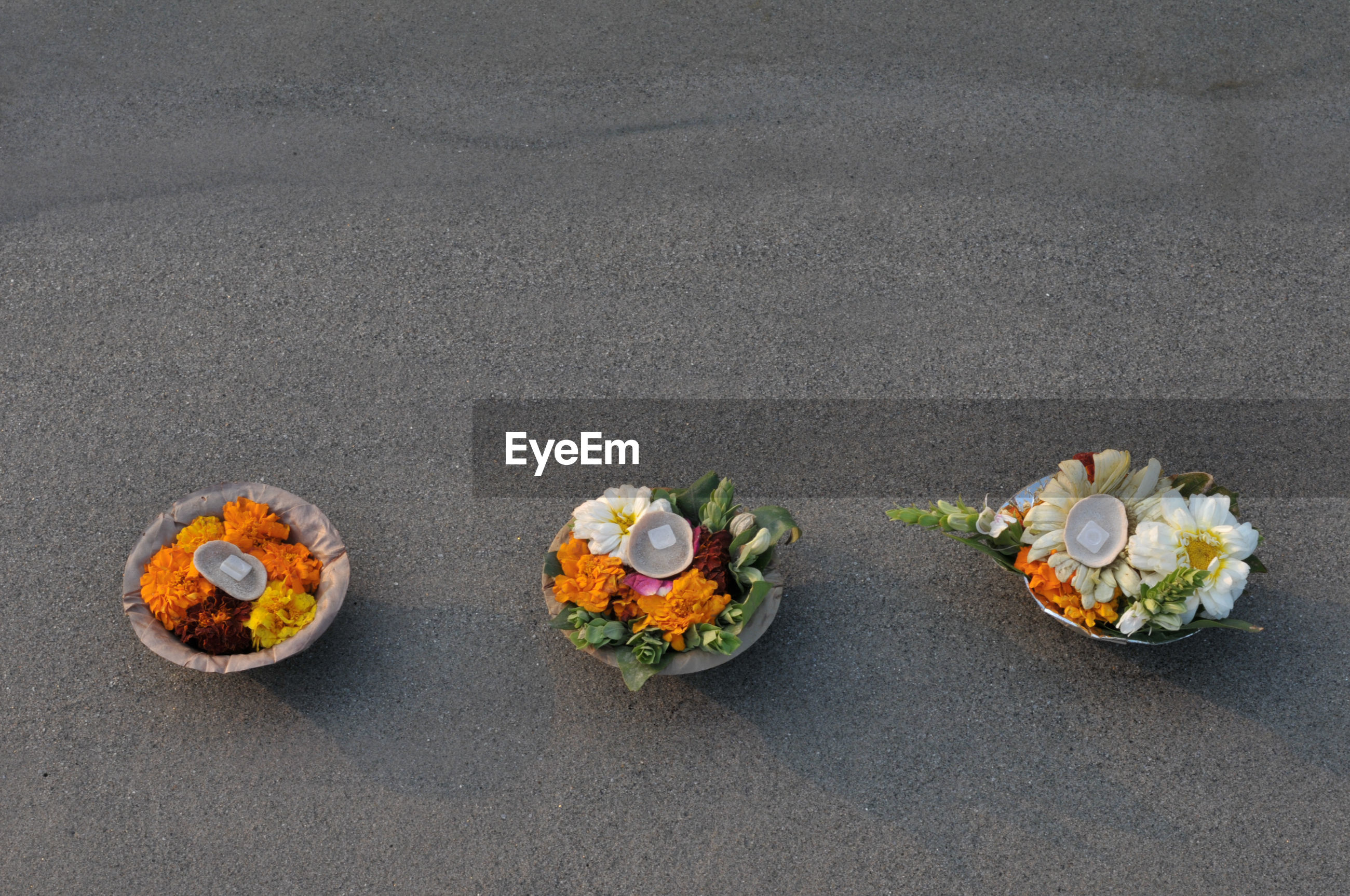 High angle view of flowers and leaves in containers on sand