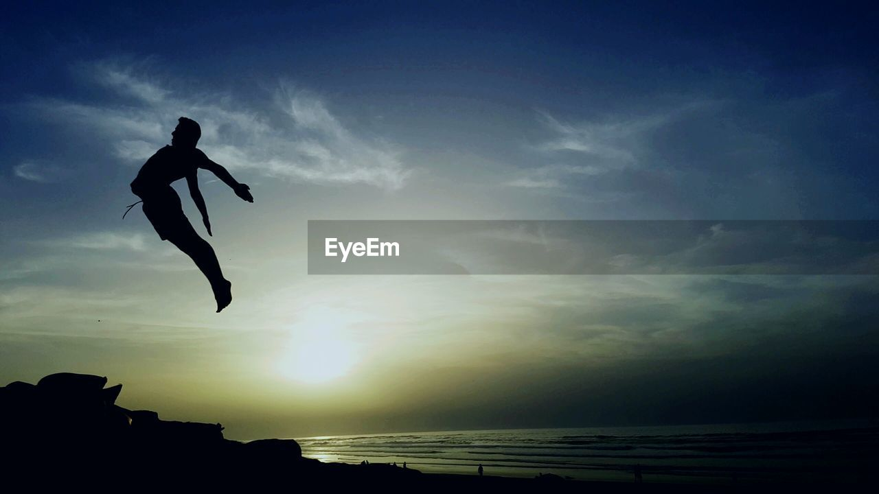 silhouette, sea, mid-air, one person, sunset, full length, sky, water, leisure activity, outdoors, nature, horizon over water, energetic, real people, scenics, beach, jumping, vacations, cloud - sky, men, lifestyles, adventure, motion, beauty in nature, day, people