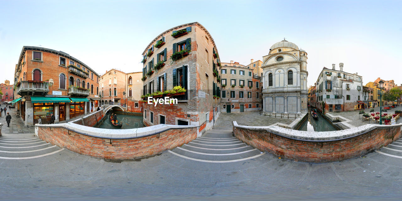 Fish-eye view of canal amidst buildings in city against clear sky