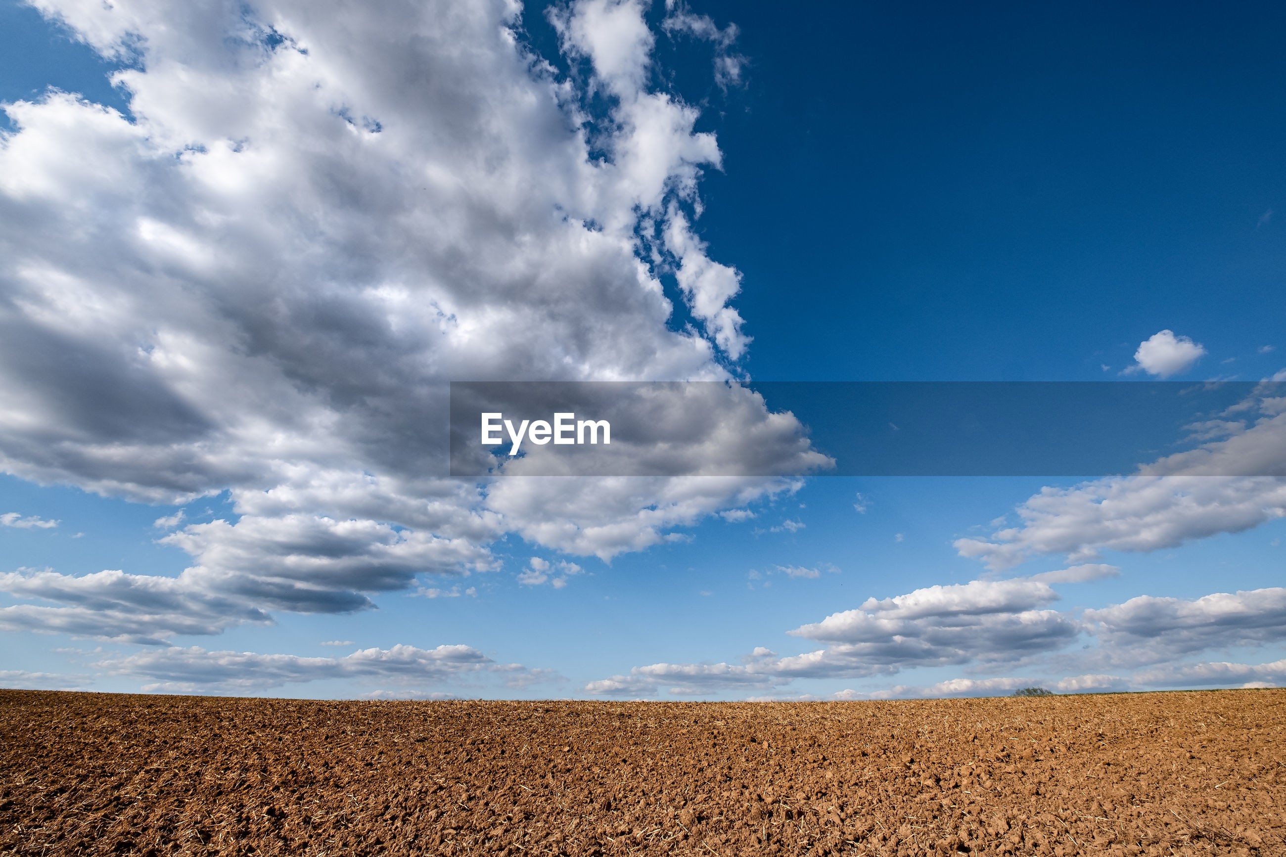 Scenic view of bare field under blue sky with dramatic clouds