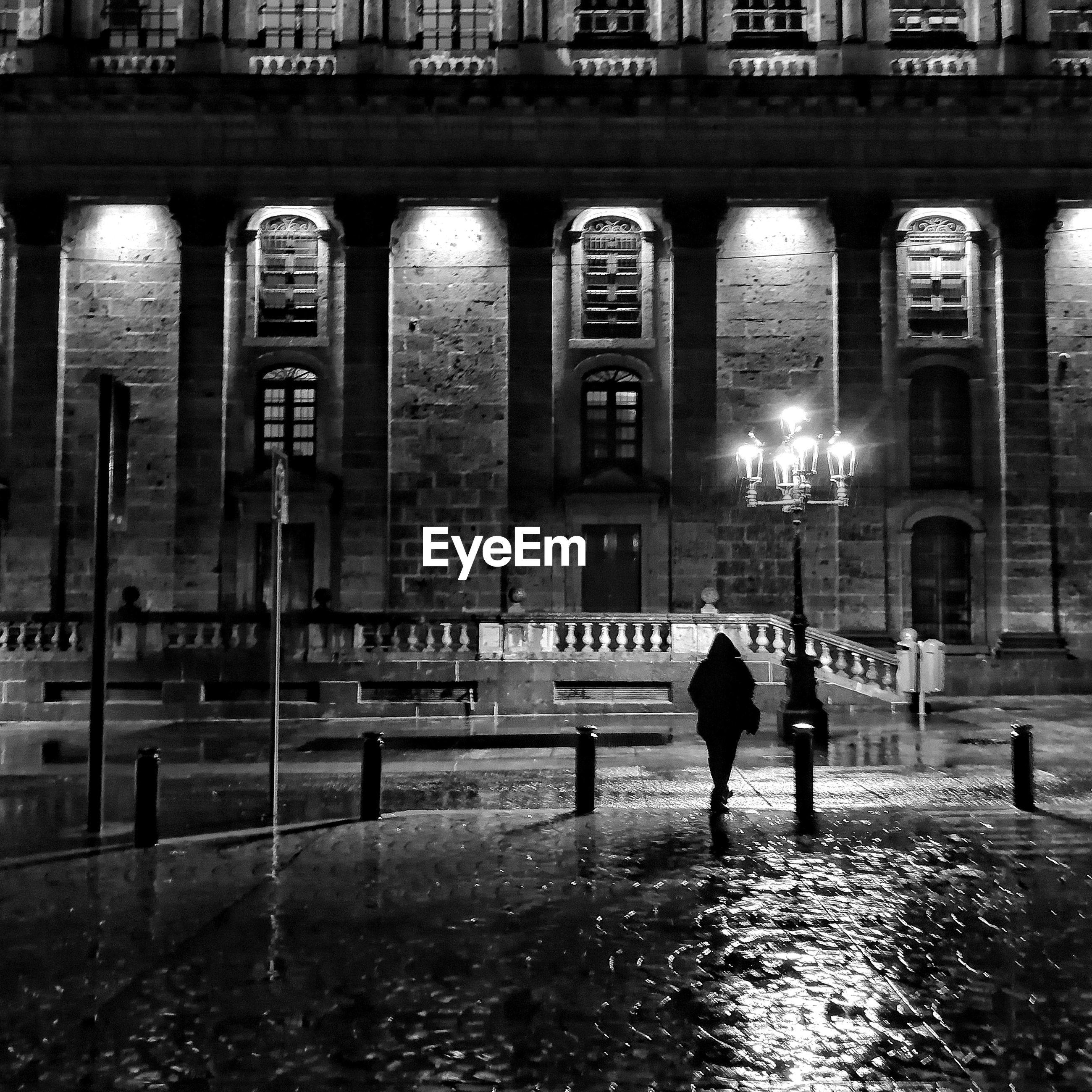 REAR VIEW OF WOMAN WALKING ON STREET IN RAIN