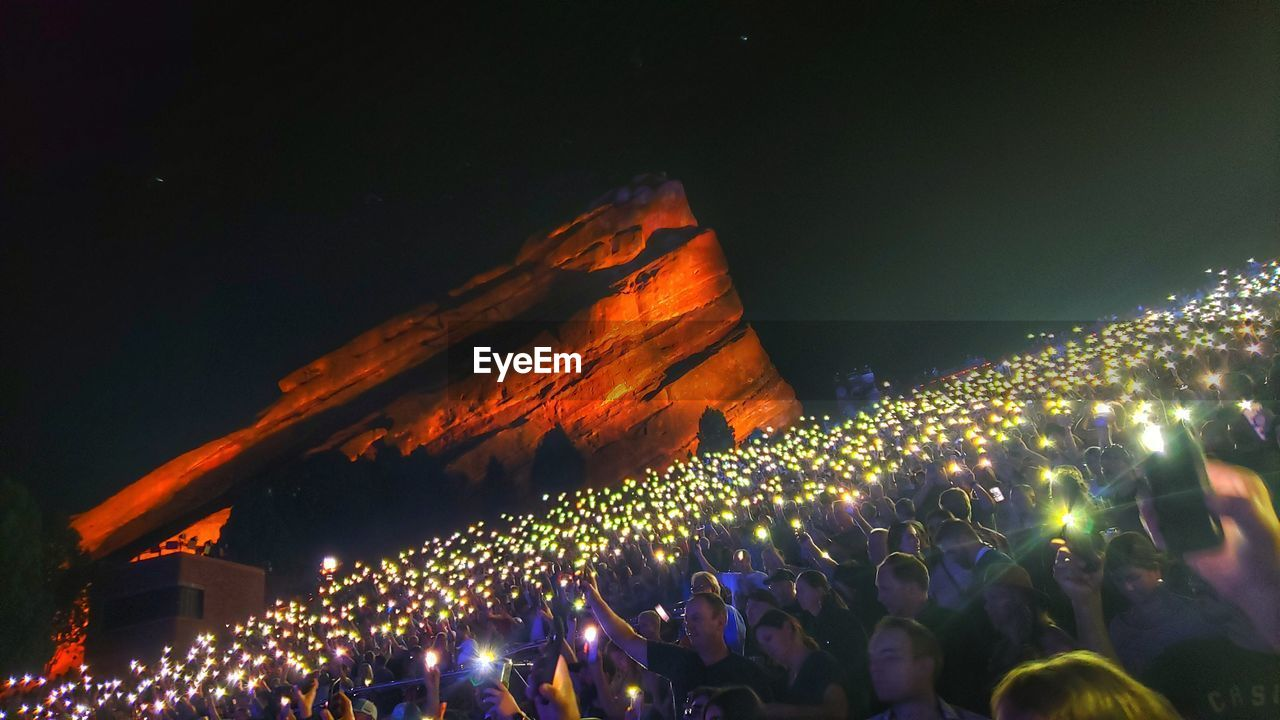 High angle view of man of people holding flashlight at music concert