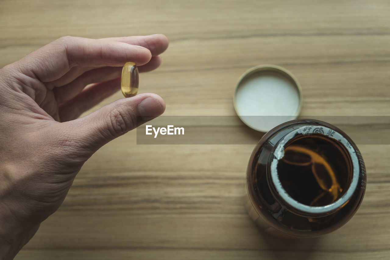 Yellow transparent omega 3 capsules in hand. taking medications. nutritional supplements