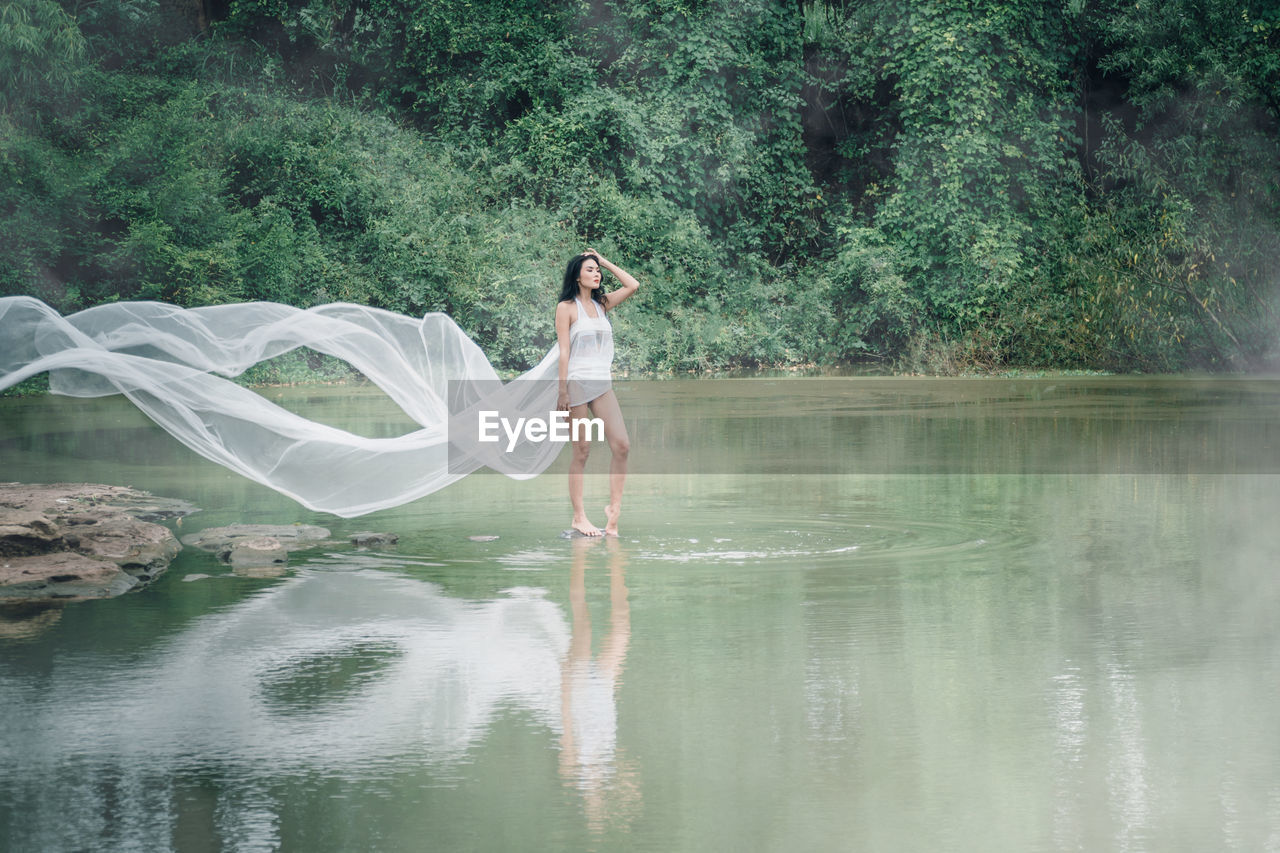 Full Length Of Woman Wearing White Dress Standing By Lake