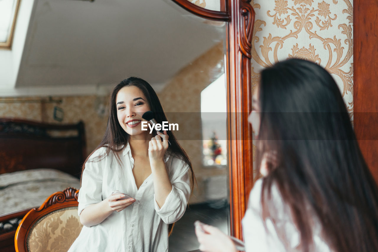 Beautiful woman applying lipstick in front of mirror at home
