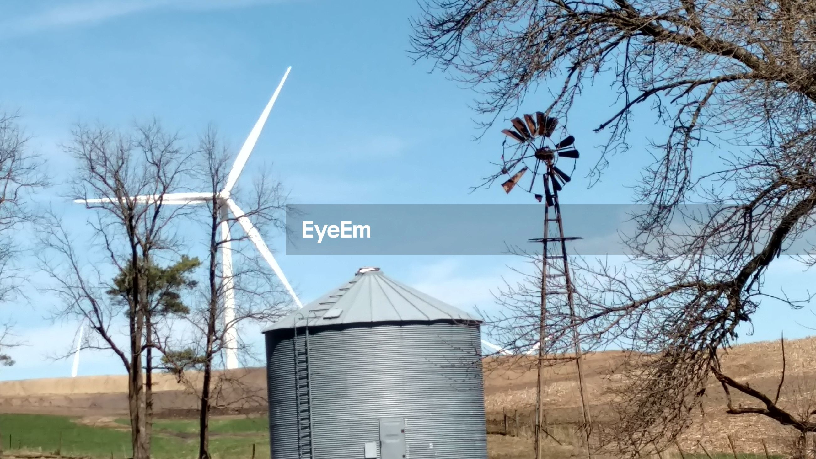 renewable energy, alternative energy, turbine, wind turbine, fuel and power generation, environmental conservation, wind power, sky, tree, plant, environment, landscape, built structure, nature, bare tree, day, rural scene, no people, building exterior, field, outdoors