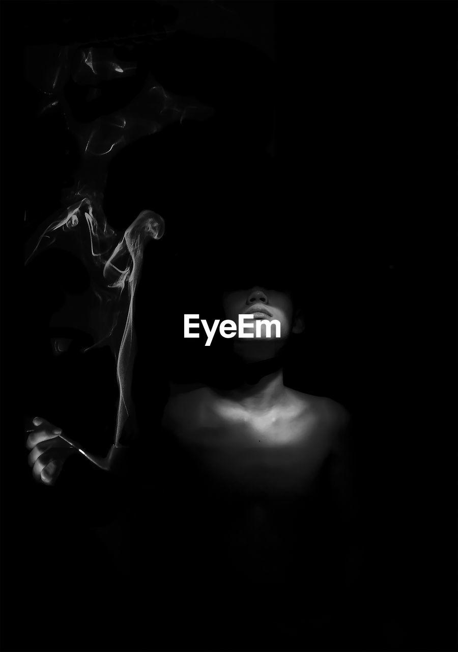 Shirtless man smoking pipe against black background