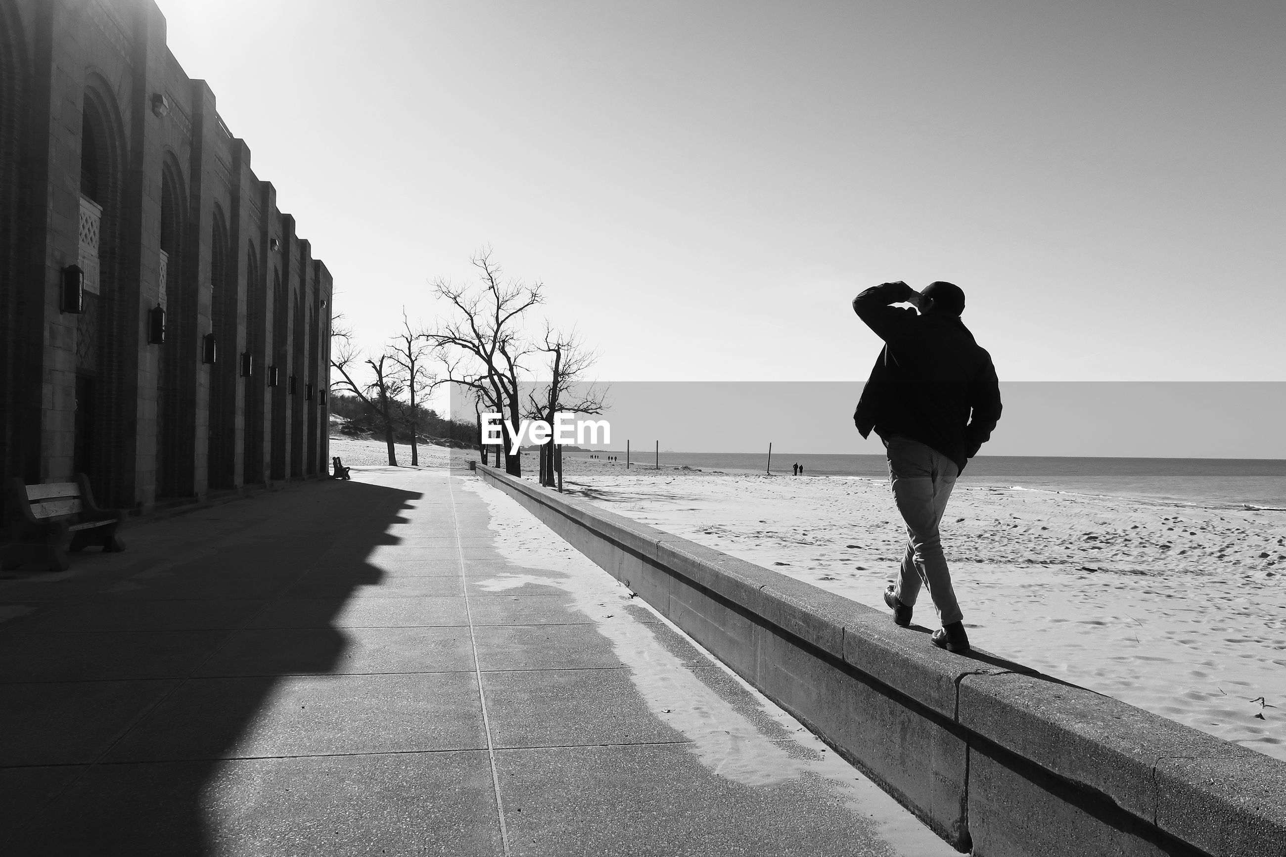 Rear view of man walking on retaining wall at beach against sky