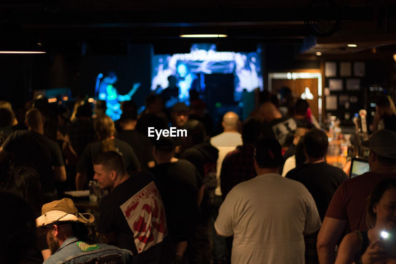 People Enjoying In Pub At Night
