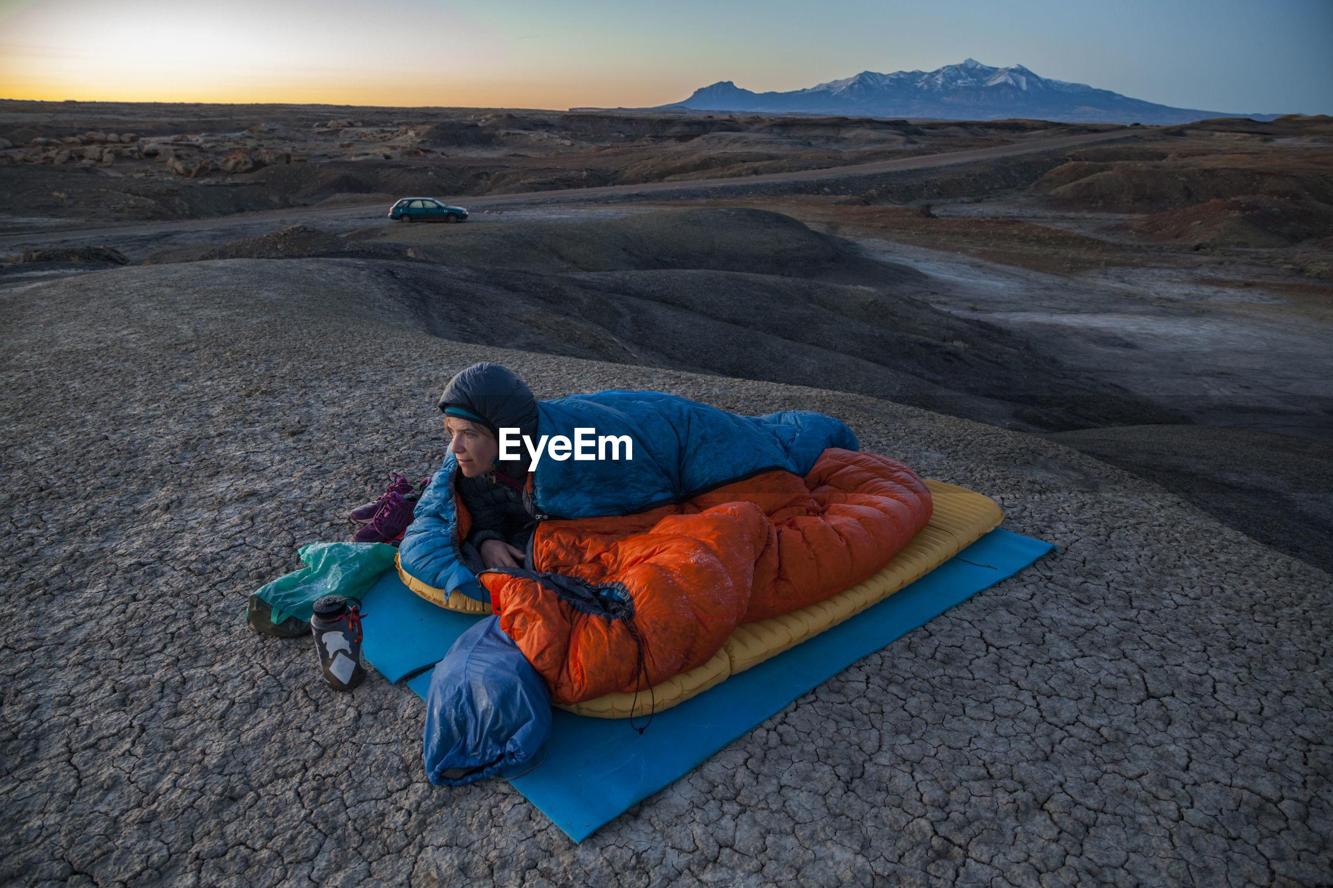 MAN LYING ON ROCK AGAINST SKY