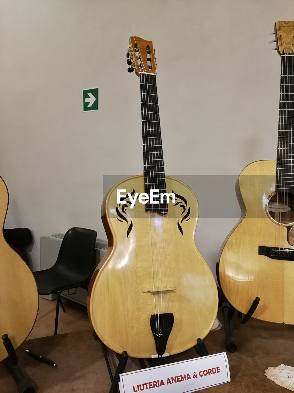 musical instrument, music, string instrument, musical equipment, guitar, indoors, arts culture and entertainment, musical instrument string, string, no people, wall - building feature, still life, electric guitar, wind instrument, acoustic guitar, wood - material, text, close-up, fretboard, woodwind instrument
