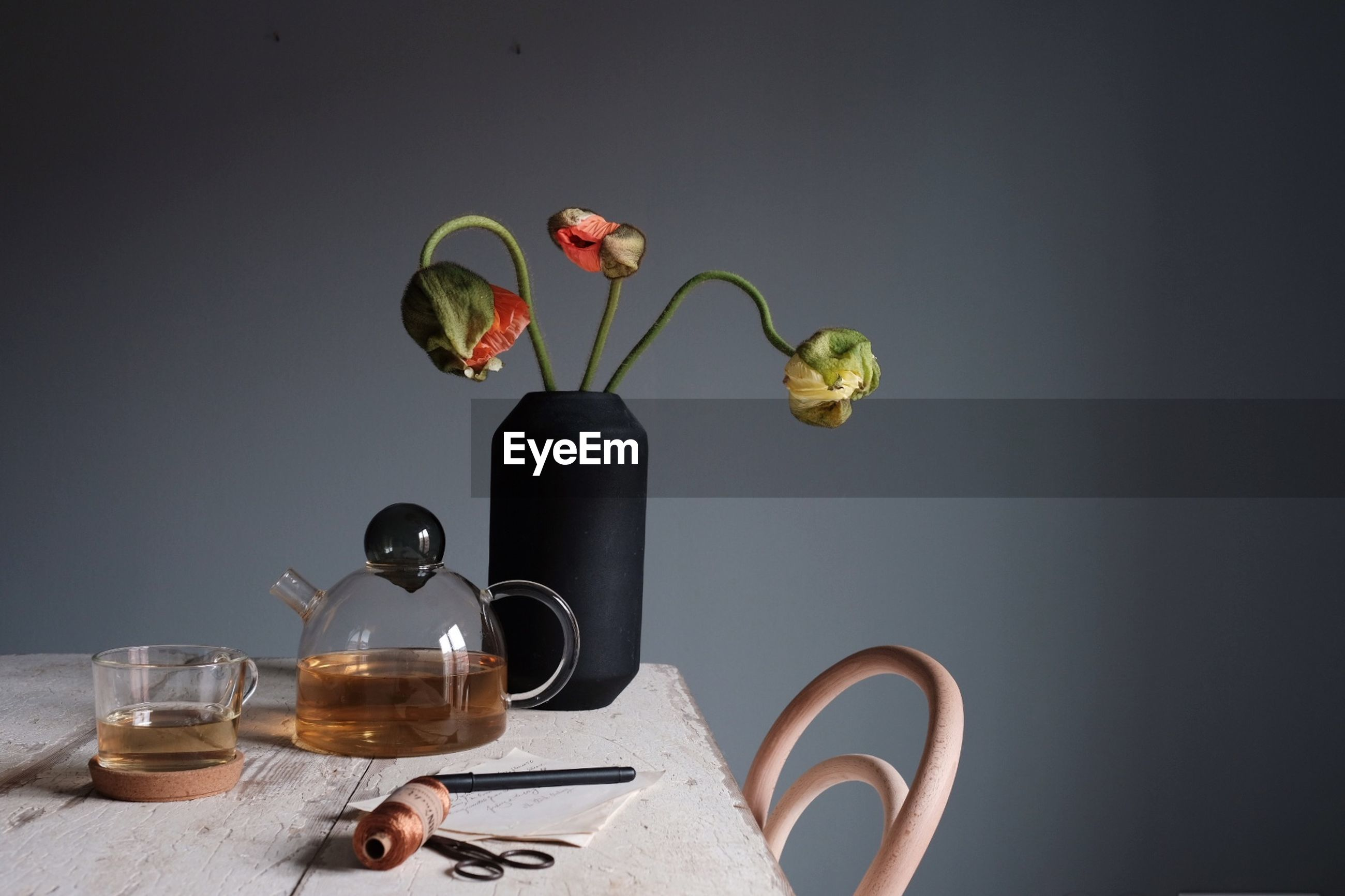 Close-up of tea and vase on table against gray wall